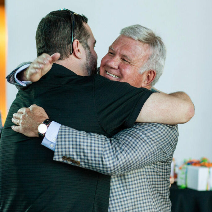 Axcet HR two men hugging anniversary party